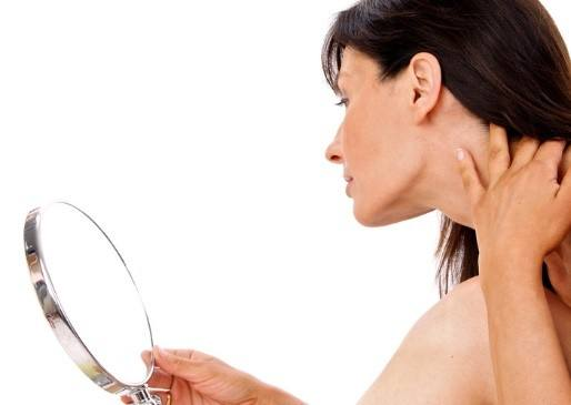 Woman looking in mirror at jawline
